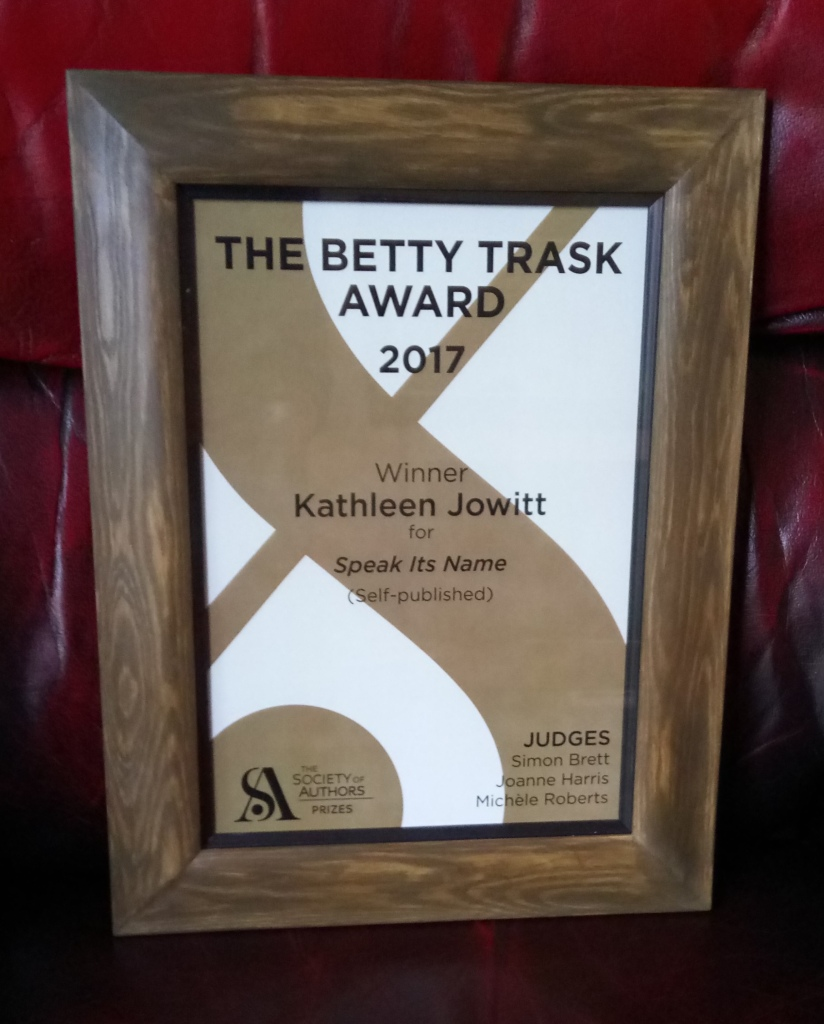 Framed certificate with text: 'The Betty Trask Award 2017/Winner/Kathleen Jowitt for Speak Its Name (self-published)/The Society of Authors Prizes/Judges/Simon Brett/Joanne Harris/Michele Roberts'