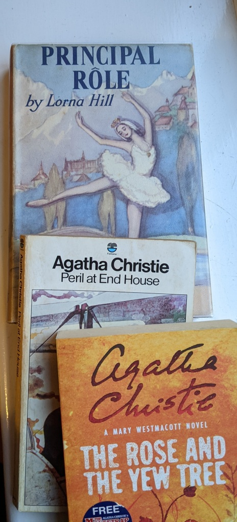 Stack of books: Principal Role by Lorna Hill (with a dustjacket with a ballerina in front of a backdrop showing an Alpine village), Peril at End House by Agatha Christie, and The Rose and the Yew Tree by Agatha Christie writing as Mary Westmacott