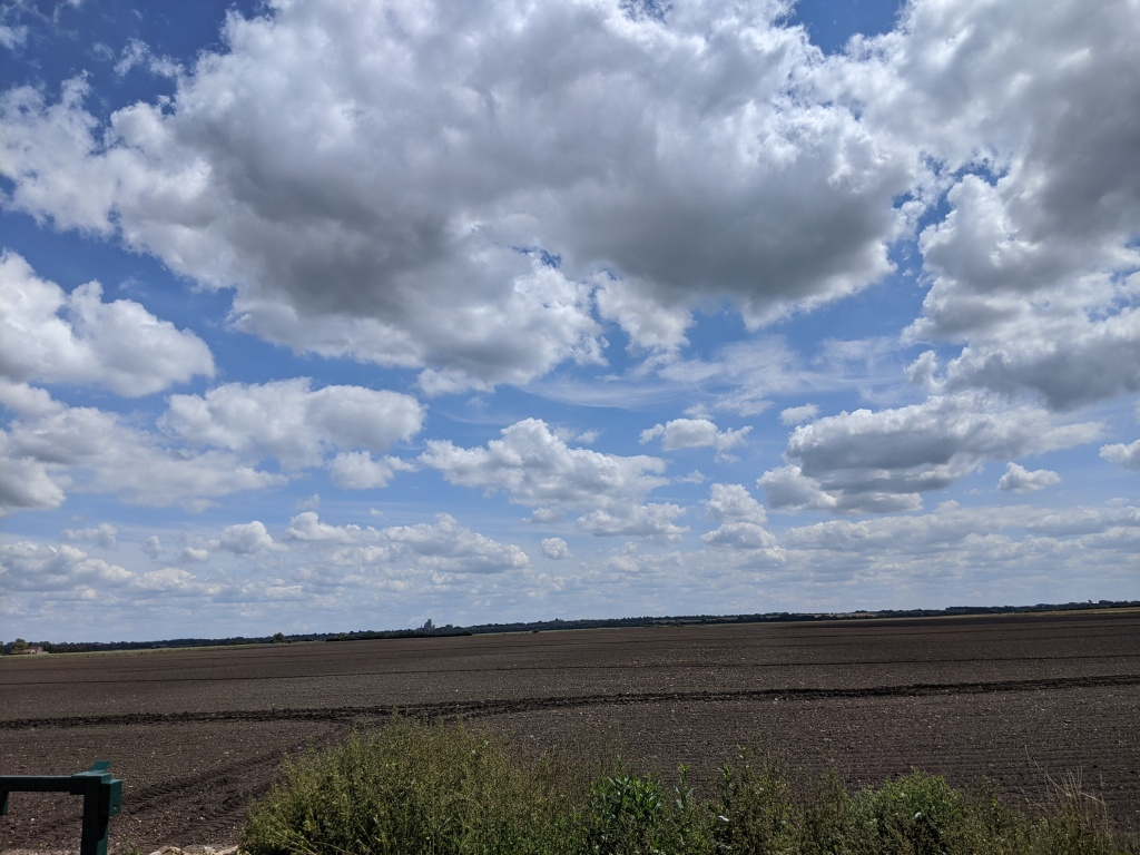 Huge pearly grey-white clouds against a blue sky, over a dark brown ploughed field