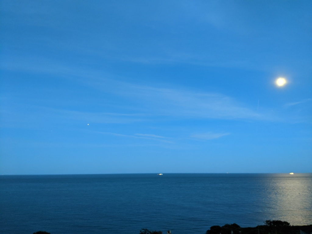 Seascape at twilight with a bright full moon lighting up a stretch of sea at the right of shot, two ships, and, at the left, one bright speck, and one just-visible point of light