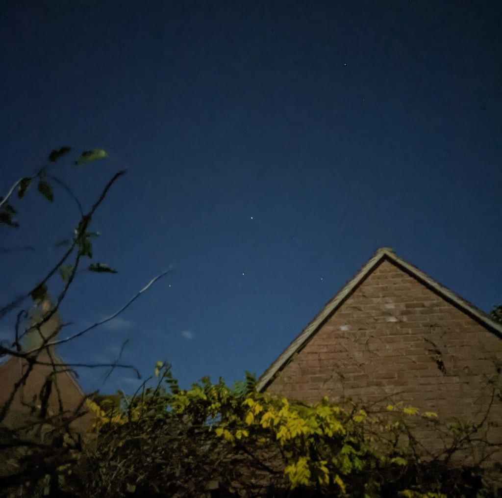 a deep blue night sky with three stars in an inverted T shape seen over a pitched roof