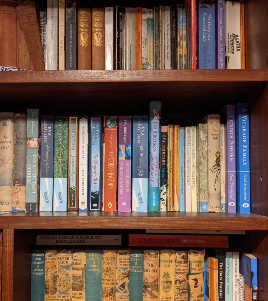 three shelves of books; authors include Arthur Ransome, John le Carré, Eva Ibbotson, Noel Streatfeild, Lorna Hill, C. S. Lewis, Charlotte Brontë, and others