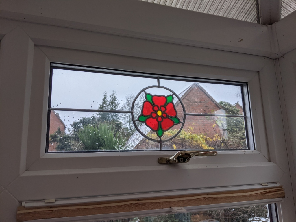 A fanlight with a red rose of Lancaster in stained glass