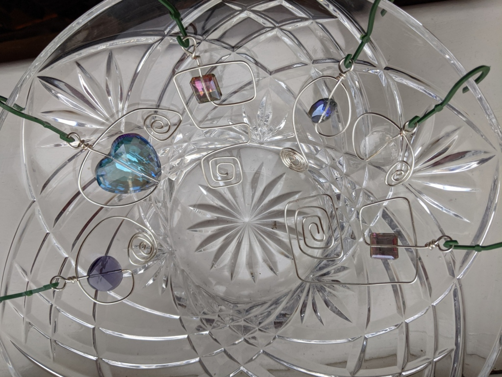 hanging ornaments made from faceted glass beads and spirals of silver-coloured wire arranged around the rim of a crystal glass bowl