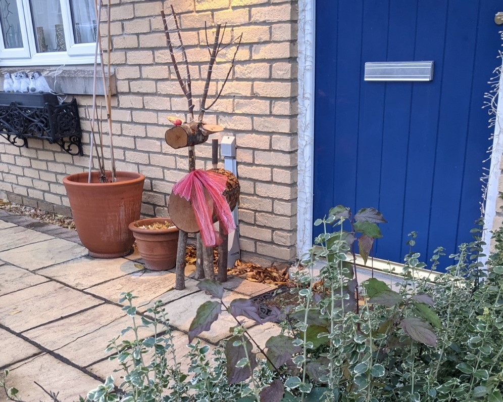 Model reindeer made from logs and twigs of wood, wearing a red bow around its neck, standing outside a blue door.