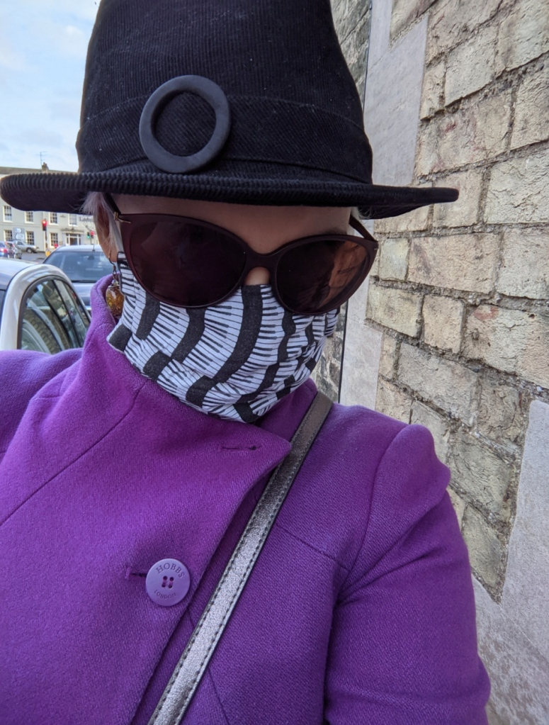 person with face almost obscured by - from the top - a black trilby hat, a pair of sunglasses, and a face mask with a pattern of black and white piano keys. Also wearing a bright purple coat
