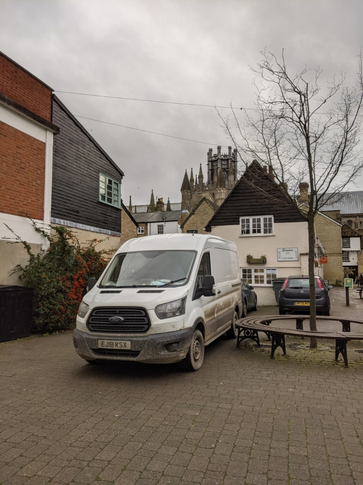 White van parked next a bench. The octagon of Ely cathedral is visible in the background.