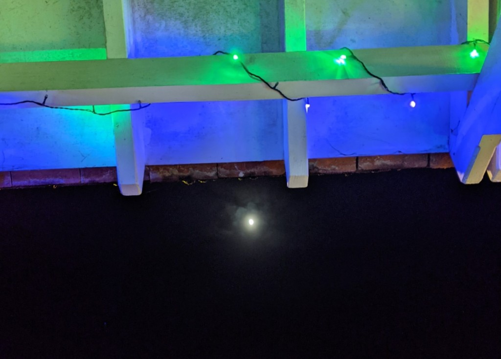 waxing gibbous moon seen just below the edge of a wooden porch, which has blue and green fairy lights twined around the beam