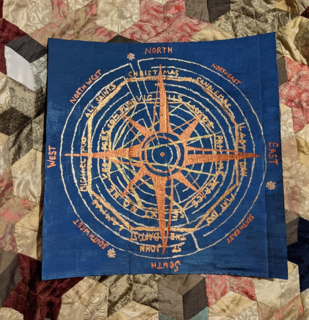 square of blue-painted cardboard with a compass rose, labyrinth, stylised shell, and the names of the monastic hours and the quarter and cross-quarter days added in metallic paint