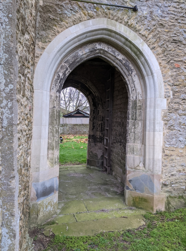Grey stone building with an arch that leads through it to another arch and a grassy space beyond.
