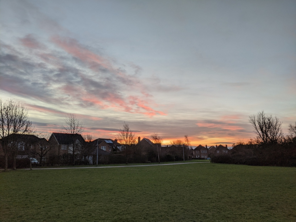 Pale blue morning sky with moody purple, pink and apricot clouds over twentieth century detached houses, bare winter trees, a shining tarmac path, and dull grass