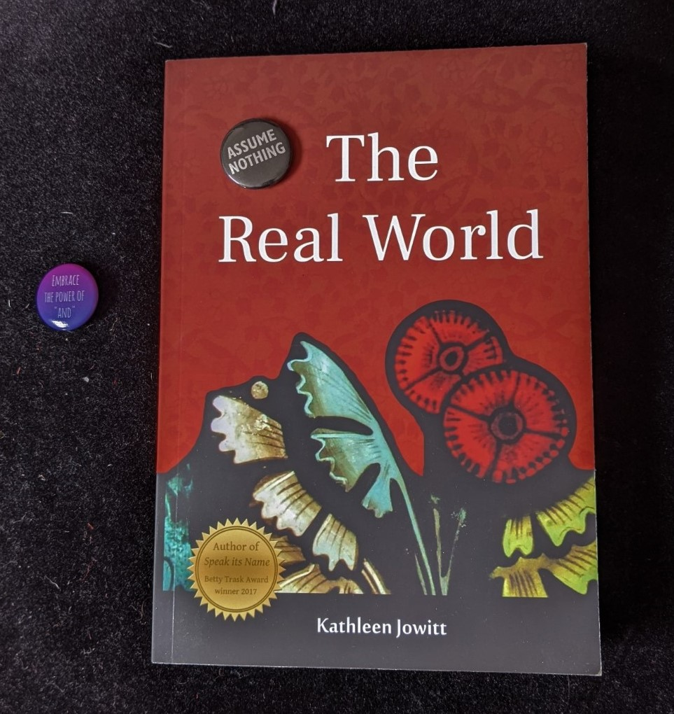 "'The Real World' with two pin badges, one reading 'EMBRACE THE POWER OF ""AND""' and the other, 'ASSUME NOTHING'"