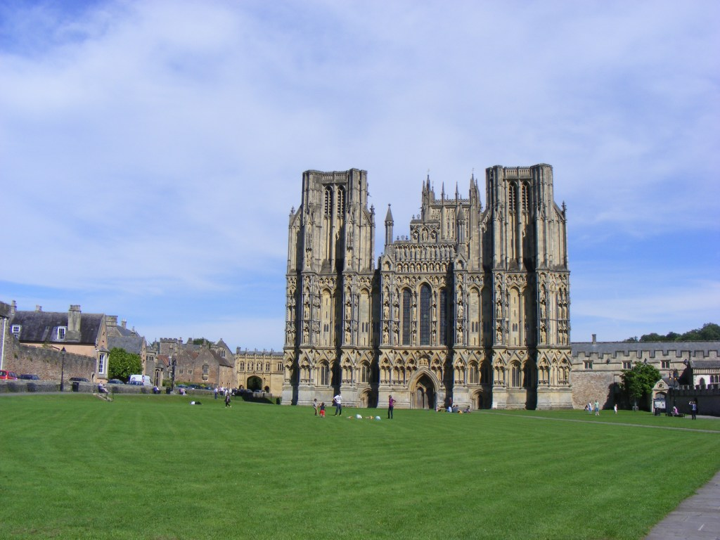 West front of a cathedral with two west towers and one central one in yellow-grey stone, seen across a broad grass green