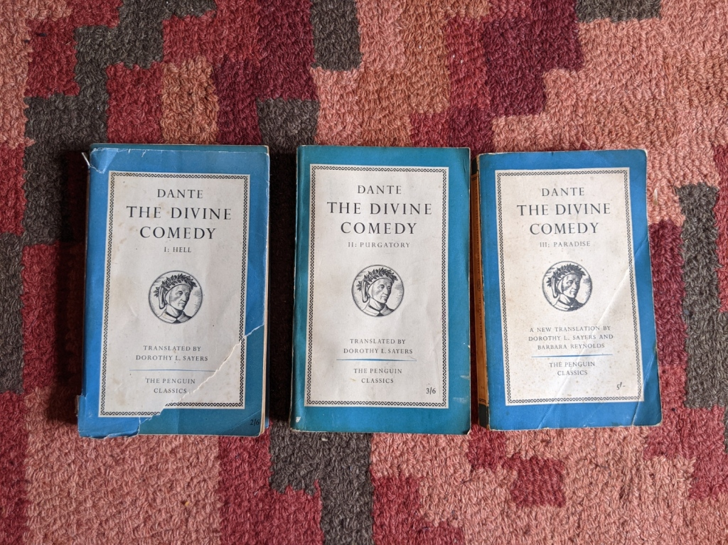 The Divine Comedy by Dante Alighieri, translated by Dorothy L. Sayers and Barbara Reynolds, in a three volume Penguin paperback edition