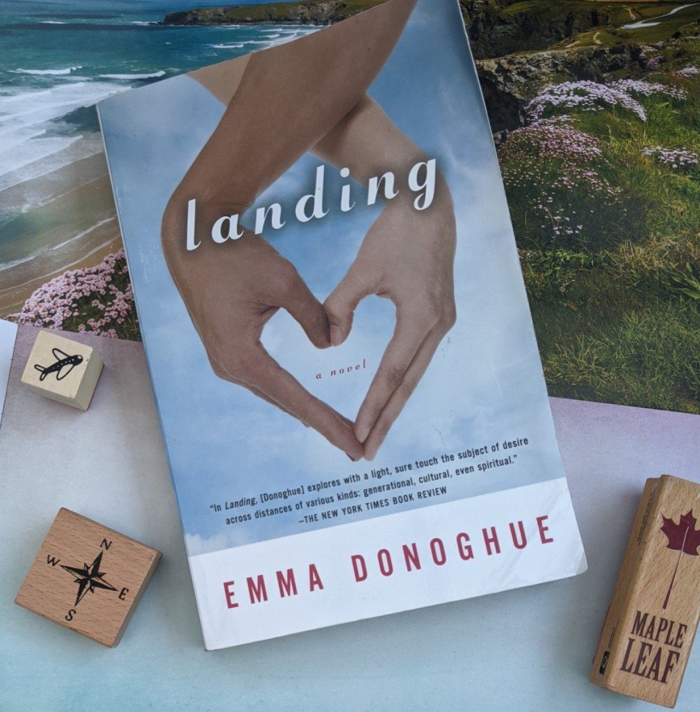 Paperback copy of 'Landing' by Emma Donoghue, with a coastal scene and wooden blocks with pictures of an aeroplane, a compass rose, and a maple leaf