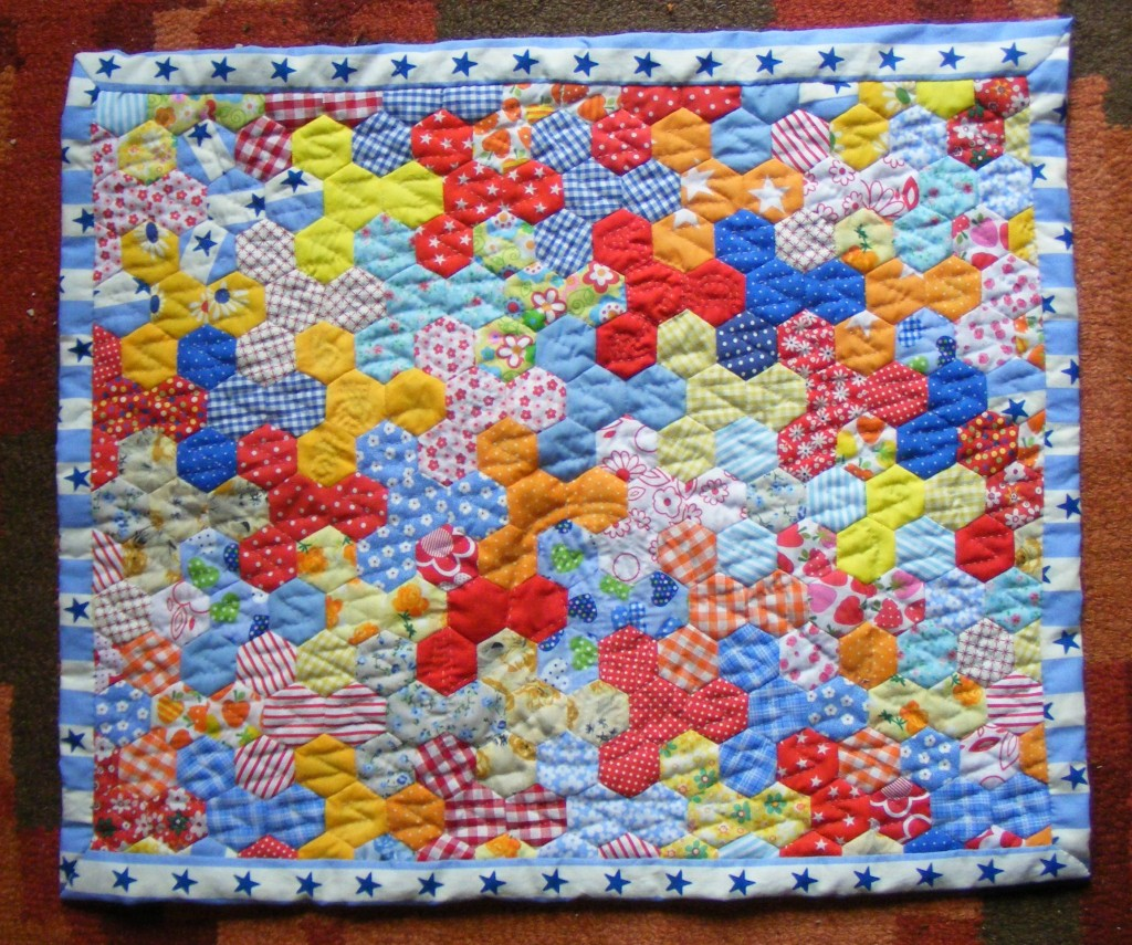 Small patchwork quilt of hexagons in primary colours