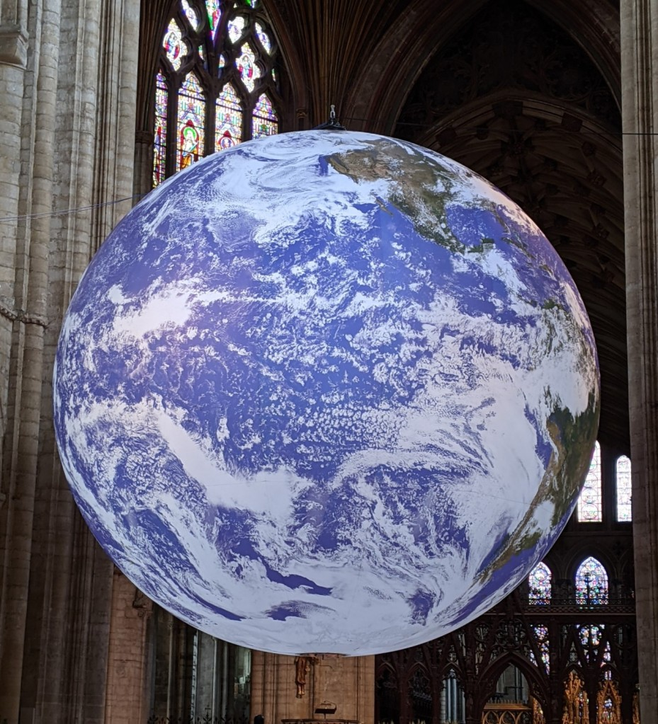 A model of planet Earth hangs in the nave of a cathedral